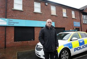 Alliance Councillor John Blair outside party leader David Ford's office, and another business which was attacked. © Presseye