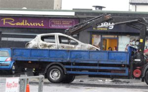 A torched car is towed away in Glengormley on Saturday morning. © Presseye